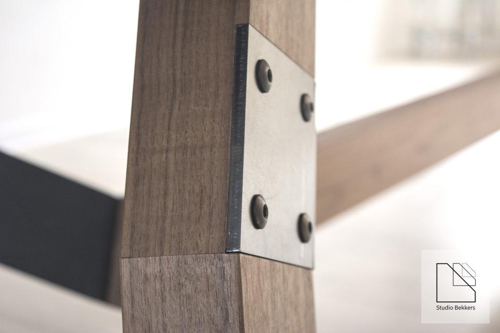 Detail tafelpoten met rauw staal en Amerikaans notenhout. Meubels van hoge kwaliteit.